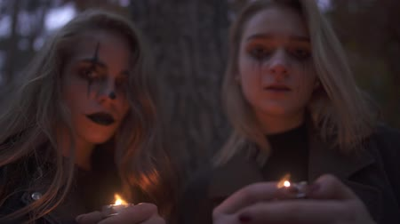 bloody hands : Portrait of two girls with halloween makeup on faces holding small candles in hands looking in camera. Horror night of gothic people. Focus changing. Bottom view
