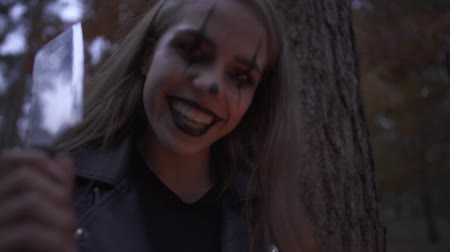 scary clown : Crazy young woman with Halloween clown makeup on her face holding big knife and small candle in hands. The girl is smiling then looking angrily. Horror night of gothic lady