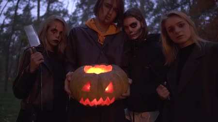 маска : Tall handsome man holding halloween pumpkin with a light inside close up, three pretty girls standing near. People with scary makeup on faces looking into camera with evil looks. Bottom view Стоковые видеозаписи
