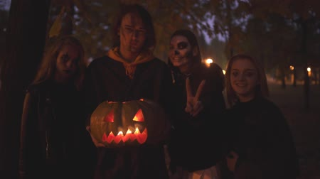маска : Four caucasian friends celebrating all saints night. Group of young people with a scary Halloween make-up in the night park holding a pumpkin with a candle inside.