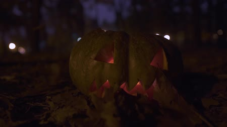 маска : Close-up of a pumpkin with the burning candle inside. Yellow autumn leaves flying around in the autumn park at night. Halloween celebration.