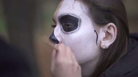 обряд : Halloween. Makeup artist applies make-up to female face Стоковые видеозаписи