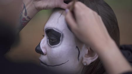 обряд : Halloween. Make-up artist applies make-up to girl face