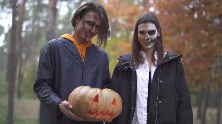 маска : Tall handsome man holding halloween pumpkin with a light inside, pretty girl standing near, both smiling then making evil faces. People with scary makeup on faces looking into camera in the forest