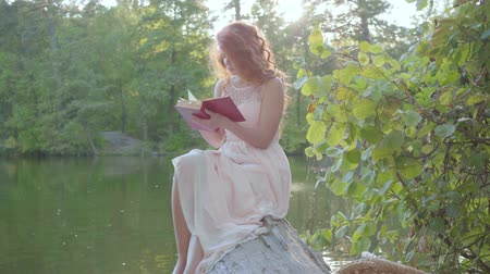 ninfa : Beautiful slim caucasian woman with red hair sitting on the riverbank reading the book. Leisure outdoors. Education concept. Connection with nature. Rural life