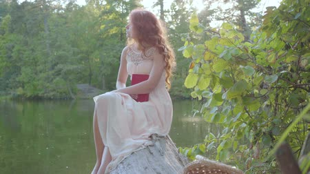 nimf : Redhead caucasian woman is sitting on the log at the riverbank holding a book with dark red cover. Intelligent and beautiful fairytale girl thinking over the writing. Stockvideo
