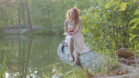 nimf : Charming redhead caucasian woman in white long dress sitting on the bank of the lake reading the book in dark red cover. Lovely fairy girl spending last warm autumn days outdoors.