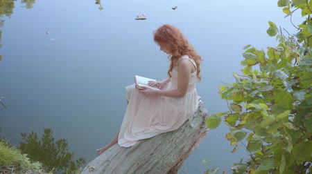 ninfa : Young charming girl with long red hair in light pink dress is reading poetry at the bank of a blue lake. Attractive caucasian woman sitting in the forest on the grey log.