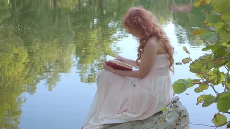 ninfa : Redhead attractive caucasian girl reading the book in dark red cover on the bank of the lake in the summer forest. Fairy woman keen on poetry.