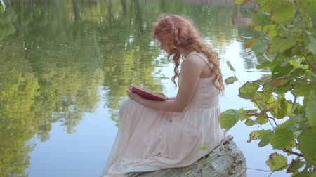 poezja : Side view of the redhead attractive caucasian girl reading the book in dark red cover on the bank of the lake in the summer forest. Fairy woman keen on poetry. Wideo