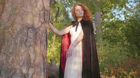 ninfe : Beautiful caucasian girl with red hair in long white dress and black gown with red lining standing next to the tree in the forest and looking away. Nymph enjoying sunny day. Filmati Stock