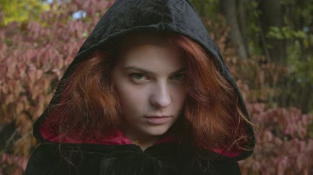 bewitch : Close-up face of attractive red-haired caucasian woman in a black gown looking at the camera. Evil witch in the autumn forest. Fairy tale, mysticism. Halloween