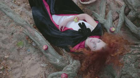bewitch : Attractive red-haired caucasian woman in white dress and black gown laying on the tree surrounded by red apples, looking at the camera. Pretty young witch resting in the autumn forest.