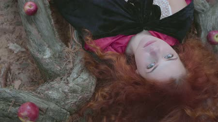 bewitch : Close-up of an attractive red-haired caucasian woman in white dress and black gown laying on the tree surrounded by red apples, looking at the camera. Pretty young witch resting in the autumn forest. Stock Footage