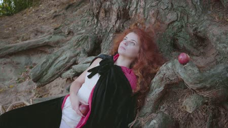 культ : Attractive slim red-haired caucasian woman in a black gown laying under the tree looking away and at the camera. Cute witch resting in the autumn forest. Snow White style.