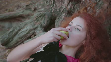 bewitch : Attractive slim red-haired caucasian woman in a black gown laying under the tree eating apple. Cute witch resting in the autumn forest. Snow White style.