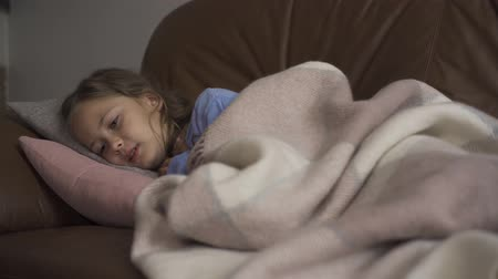 coughing : Sick young caucasian girl coughing while lying under blanket at home. The child has fever. Concept of health, illness, sickness, common cold, treatment Stock Footage