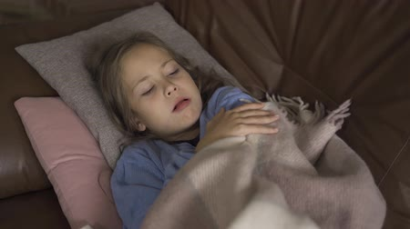 coughing : Young caucasian brunette girl in blue sweater laying under the warm blanket and coughing. Little child having fever and staying at home.