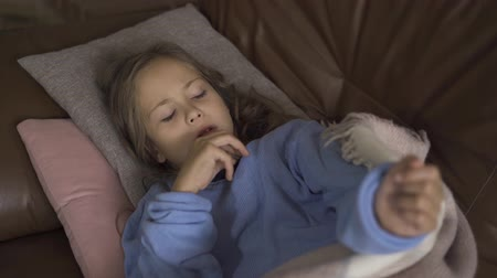medical thermometer : Young caucasian girl in blue sweater laying under the warm blanket and taking temperature. Close-up of a little sick brunette child.