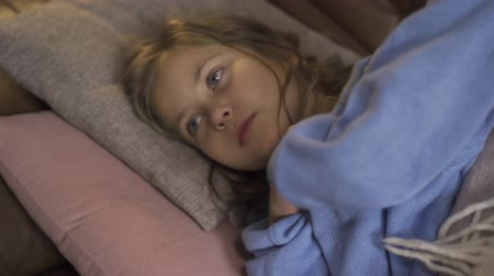 tosse : Young little girl in blue warm sweater taking temperature. Close-up of a a sad child laying at home with fever.