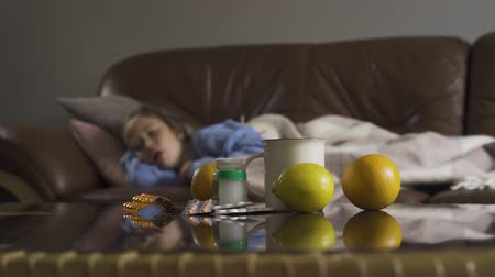 симптом : Sick young caucasian girl coughing while lying under blanket at home in the background. Pills, lemons and tea cup on the table in the foreground. Concept of health, illness, sickness, cold, treatment