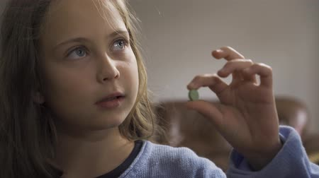 nyel : Close-up of sick little girl in blue sweater examining the green pill. Caucasian child undergoing treatment at home.