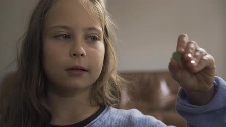 nyel : Close-up of little caucasian girl with grey eyes dressed in blue sweater taking the green pill. Caucasian kid undergoing treatment at home.