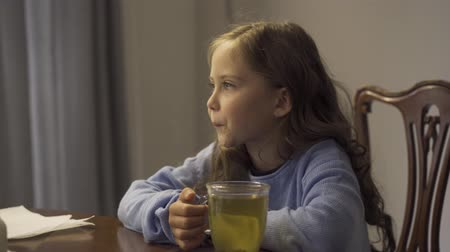 baca : Cute little girl drinking herbal tea while sitting at the table at home. The child enjoying tea for colds in the kitchen. Carefree childhood. Concept of healthcare