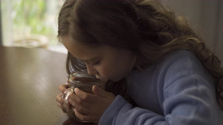 baca : Little caucasian girl with long curly hair blowing on the cup of chamomile tea. Cute sad brunette child dressed in blue sweater waiting for her hot drink to cool.