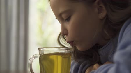 canna fumaria : Close-up of a little caucasian girl with long curly hair blowing on the cup of chamomile tea and tasting it. Cute sad brunette child dressed in blue sweater waiting for her hot drink to cool.