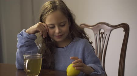 baca : Close-up of little girl holding lemon while drinking herbal tea. Child sitting at the table at home. Kid enjoying tea for colds in the kitchen. Carefree childhood. Concept of healthcare