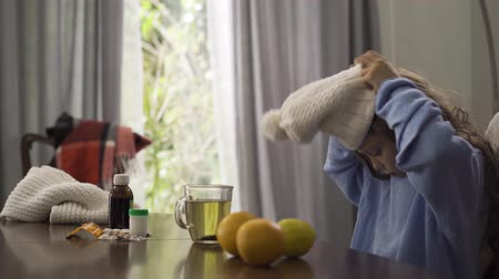 citrom és narancsfélék : Close-up of little girl putting on winter hat and scarf while sitting at the table at home. Pills, lemon, oranges and tea cup are on the table. Concept of healthcare