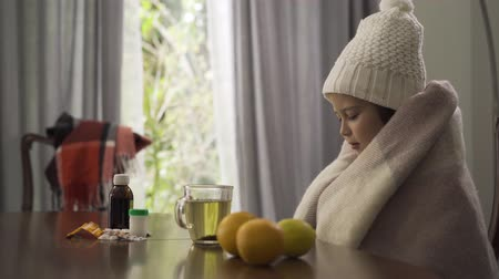 citrom és narancsfélék : Cute little caucasian girl in warm white hat and scarf covering herself with a blanket. Child sitting at the table with pills, lemon and oranges. Concept of illness, sickness, treatment. Stock mozgókép
