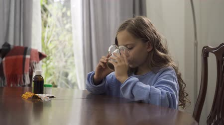 citrom és narancsfélék : Cute little girl drinking herbal tea while sitting at the table at home. The child enjoying tea for colds in the kitchen. Pills, lemon and oranges are on the table. Concept of healthcare