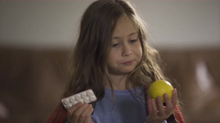 baca : Close-up face of sick caucasian girl choosing between pills and lemon and looking at camera while sitting at home. Traditional and alternative medicine. Concept of health, illness, sickness, cold, treatment