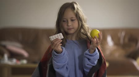 canna fumaria : Pretty child choosing between pills and lemon for the treatment. Cheerful caucasian girl deciding to take the lemon and smiling. Traditional and alternative medicine.