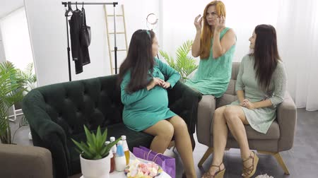 bekleyen : Two beautiful girls in light dresses chatting with their pregnant friend in the living room. Women calming down their pregnant friend before birth. Company of caucasian females celebrating the happy event.
