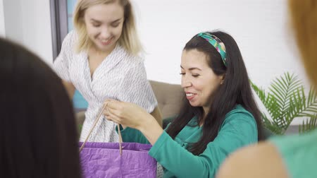 bekleyen : Young caucasian blonde girl hugging her pregnant brunette friend and giving her present in violet gift bag. Four charming women spending time with the expectant. Stok Video