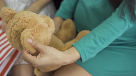 meg nem született : Close-up of soft yellow teddy bear. Female hands holding the gift. Pregnant woman in silk blue-green dress with a present for her unborn child. Stock mozgókép