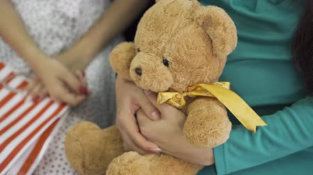 meg nem született : Close-up of soft yellow teddy bear with a silk bow. Female hands holding the gift. Pregnant woman in silk blue-green dress with a present for her unborn child.