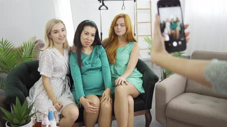 развлекательный : Three young caucasian girls taking photos sitting on the coach. Female hands shooting her friends. Company of women spending time with the expectant at pre-birth party. Стоковые видеозаписи