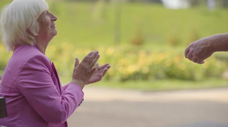 convidativo : Side view of a nice blonde mature woman sitting in the summer park and clapping her hands. Male senior hand appearing with a gesture inviting her to dance. Active life after retirement.