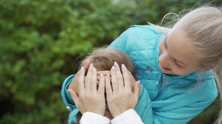 vnouče : Young blond teen creeping to a brunette senior woman from the back and closing her eyes with hands. Cheerful granddaughter surprising her grandma. Family meeting outdoors. Dostupné videozáznamy