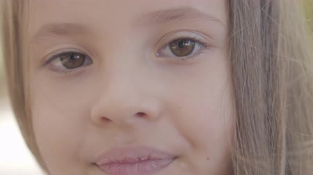 gözlü : Close-up of a young beautiful brown-eyed girl with brunette hair smiling to the camera. Innocent caucasian child standing in the autumn park. Stok Video