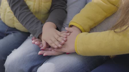 piled : Close-up of small childrens hands and adult female palms stacked on top of each other. Unity of a happy caucasian family.