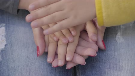 piled up : Close-up of familys hands stacked carefully on top of each other. Small childrens hands and adult female palms symbolizing unity. Stock Footage