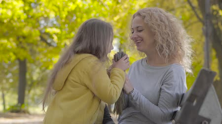 darovat : Two little cute caucasian sisters giving their mom flowers and kissing her. Pretty blond curly woman enjoying holidays with her lovely daughters in the autumn park.