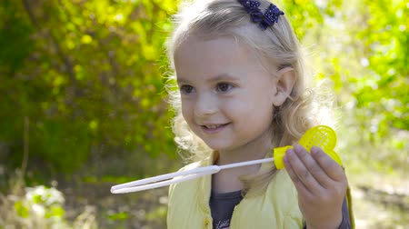 explodindo : Close-up of a charming blond girl staying in sunrays and blowing soap bubbles. Little child with brown eyes playing in the park and smiling.