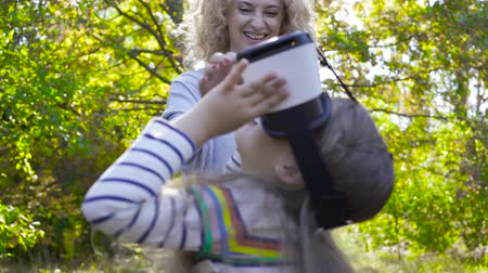 blúz : Side view of brunette caucasian girl in VR glasses dressed in striped blouse. Her cheerful mother staying behind, talking to her and laughing. Child playing with virtual reality headsets outdoors.