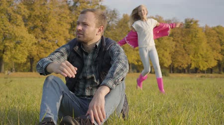 sorprendente : Smiling caucasian girl running to a man sitting on the autumn meadow. Blonde teen daughter dressed in casual clothes and pink rubber boots closing her fathers eyes with hands.